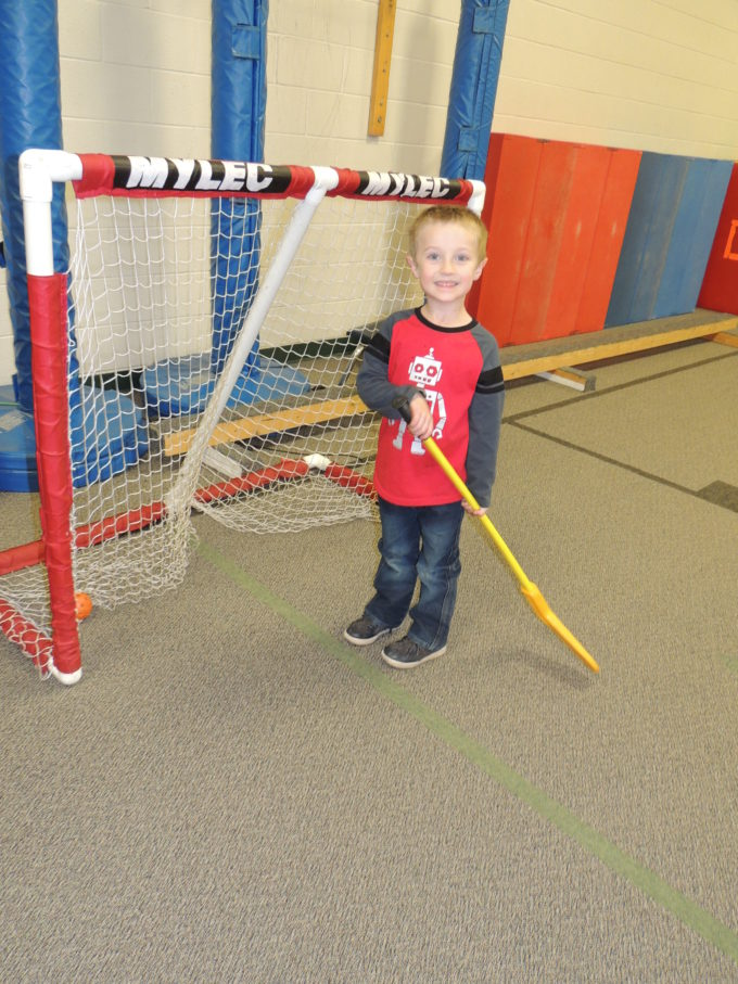 student standing in front of hockey net holding hockey stick