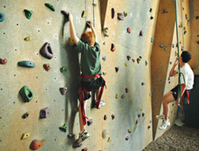 teen climbing an indoor rock wall